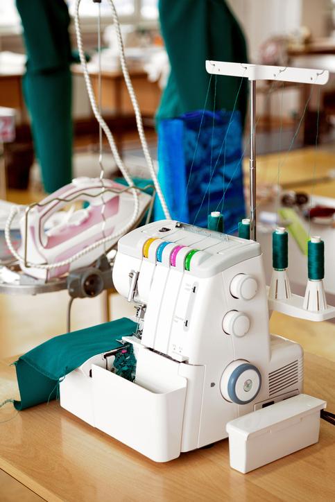 Overlock sewing machine in tailor office. Fashion designer equipment serger