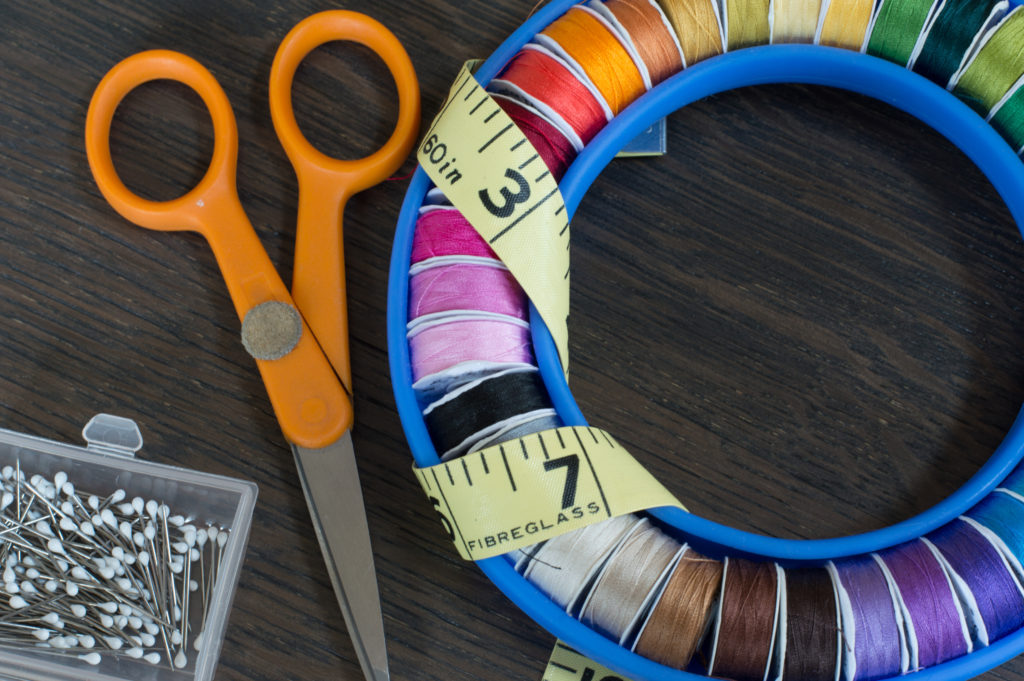 Close up of coloured sewing bobbins in a round holder with measuring tape, scissors and pins on a brown background oak table.